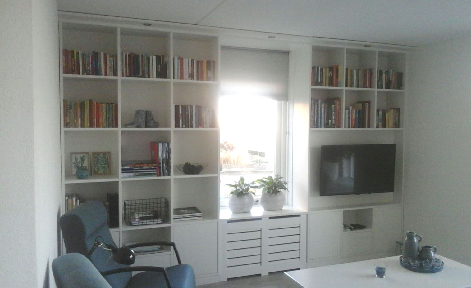 Kastenwand met radiatorombouw en tv ruimte